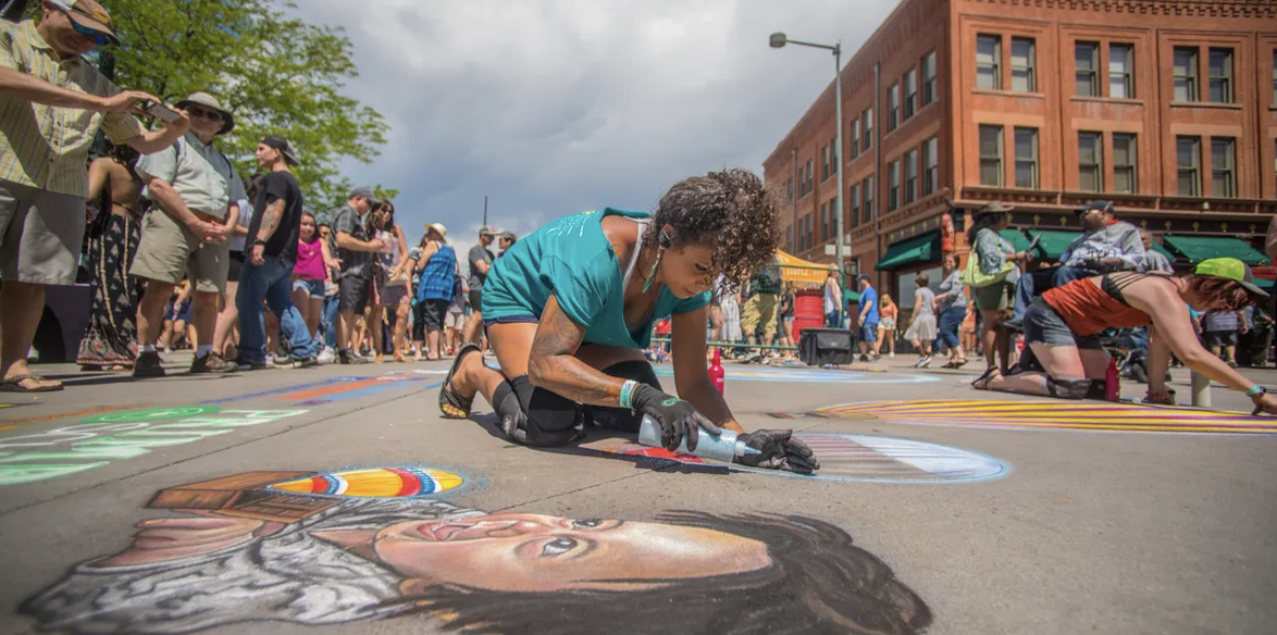 Chalk artist drawing with crowd watching
